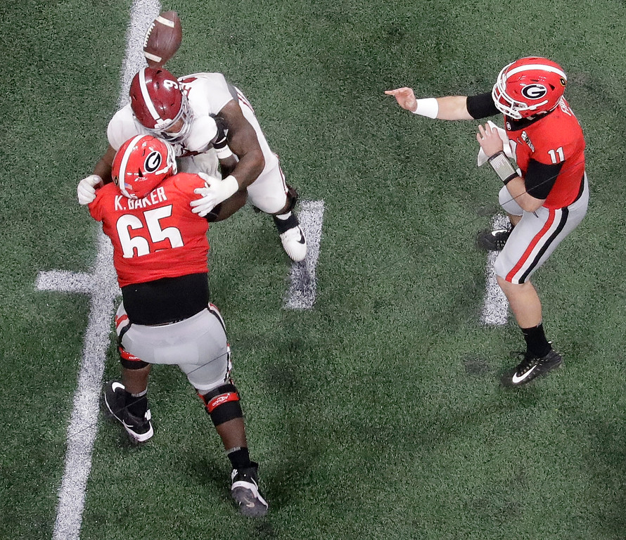 . Georgia\'s Jake Fromm throws a ball that is deflected off the helmet of Alabama\'s Da\'Shawn Hand and intercepted by Raekwon Davis during the second half of the NCAA college football playoff championship game Monday, Jan. 8, 2018, in Atlanta. (AP Photo/John Bazemore)