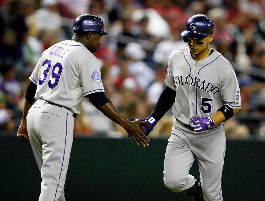 . Colorado Rockies Carlos Gonzalez (5), right, celebrates with third base coach Stu Cole (39) after hitting a solo home run in the seventh inning during a baseball game against the Arizona Diamondbacks on Saturday, July 6, 2013, in Phoenix. (AP Photo/Rick Scuteri)