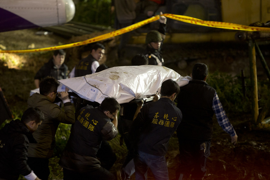 . Rescuers carry a victim from the TransAsia Airways ATR 72-600 that crashed into the Keelung river at New Taipei City on February 4, 2015. At least 23 people were killed when a passenger plane operated by TransAsia Airways clipped an overpass soon after take-off and plunged into a river in Taiwan, the airline\'s second crash in seven months.  (Photo by Ashley Pon/Getty Images)