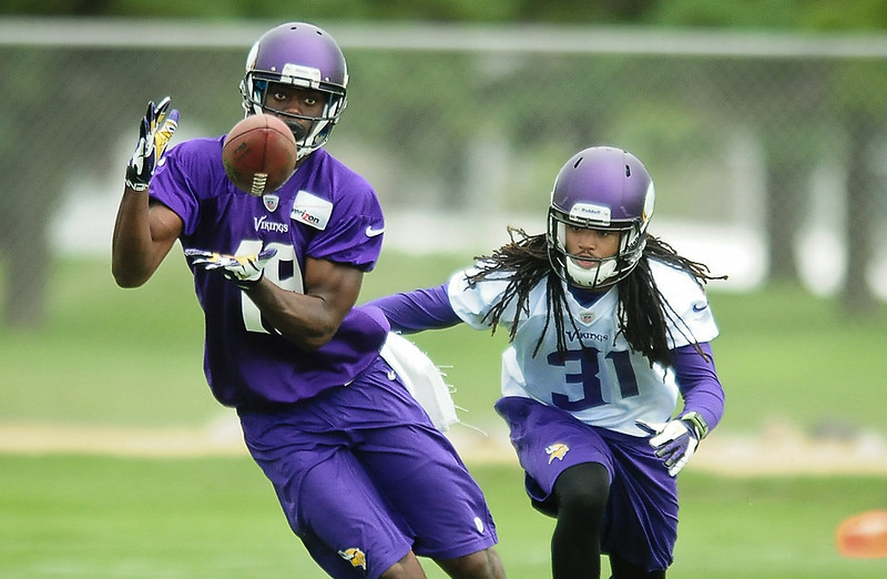 . Minnesota Vikings wide receiver Jerome Simpson, left, catches a pass under pressure from cornerback Bobby Felder at Vikings training camp in Mankato, Minn., on Friday, July 26, 2013. (Pioneer Press: Ben Garvin)