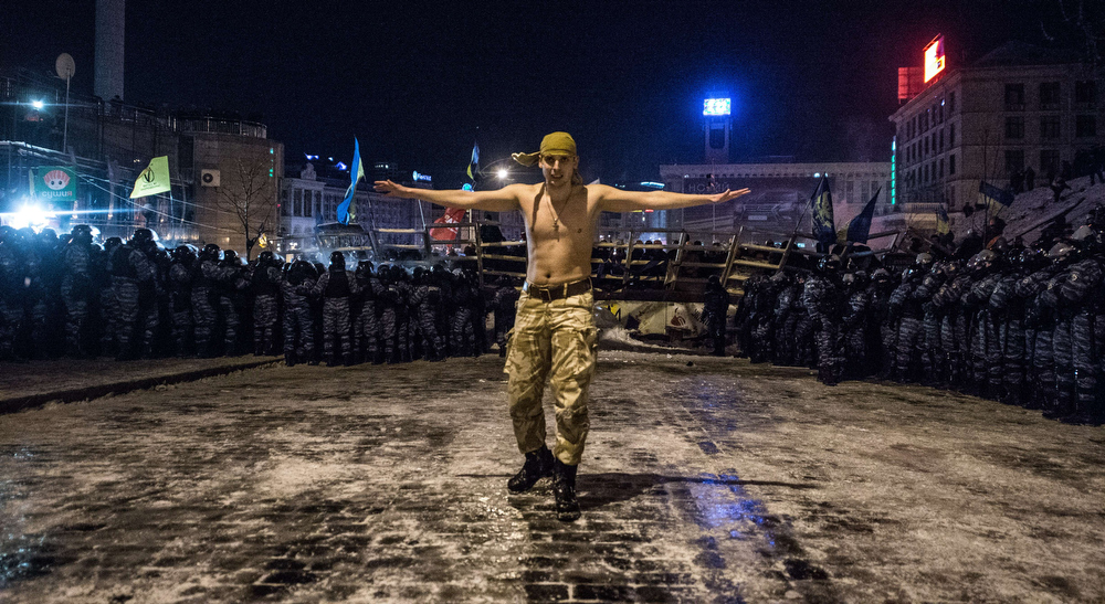 """. A protester stands next to riot policemen getting ready to launch an assault to a  barricade held by protesters on Independence Square  in Kiev late on December 11, 2013. Ukrainian security forces on Wednesday stormed Kiev\'s Independence Square which protesters have occupied for over a week but the demonstrators defiantly refused to leave and resisted the police in a tense standoff. Eite Berkut anti-riot police and interior ministry special forces moved against the protestors at around 2:00 am (midnight GMT) in a move that prompted US Secretary of State John Kerry to express \""""disgust\"""" over the crackdown. DMITRY SEREBRYAKOV/AFP/Getty Images"""