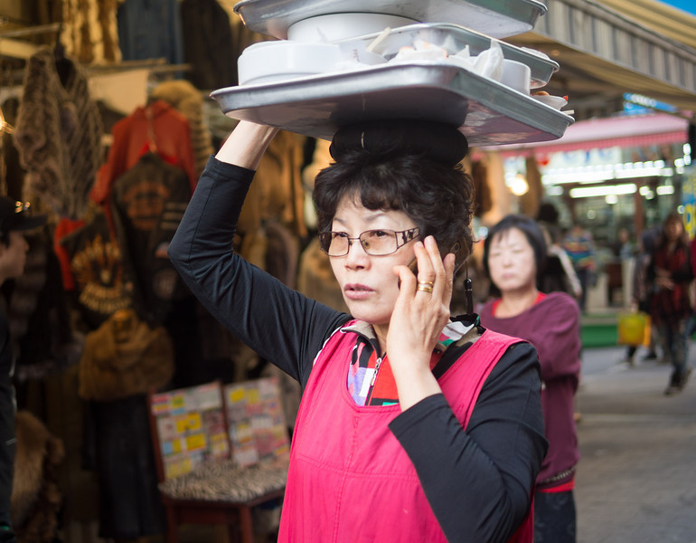 Balancing her tray while chatting on the phone. Namdaemun market, Seoul