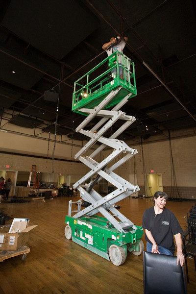Wilbert Fergeson and Anne Taylor install lighting fixtures in the new theater space.