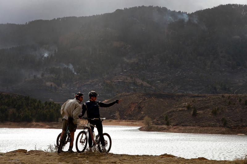 . Steve Verhow, left and Bill McKinney, right, check out  the fire from an overlook at Horsetooth Reservoir along North Colorado Road 23.  Calmer weather conditions helped keep the Galena Fire west of Fort Collins in check today March 17th, 2013.  The fire stands at 45% containment but moisture is expected in the late afternoon which should help firefighters. (Photo By Helen H. Richardson/ The Denver Post)