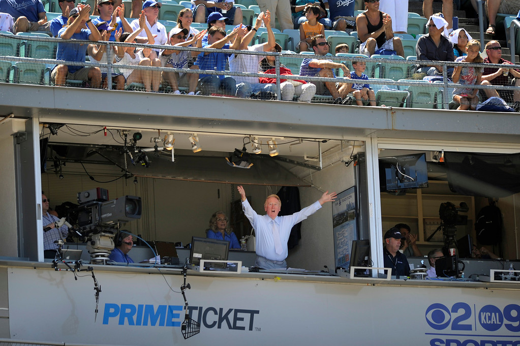 . Dodgers announcer Vin Scully waves to the crowd after it was announced he will return to the booth in 2013. (Michael Owen Baker/L.A. Daily News)
