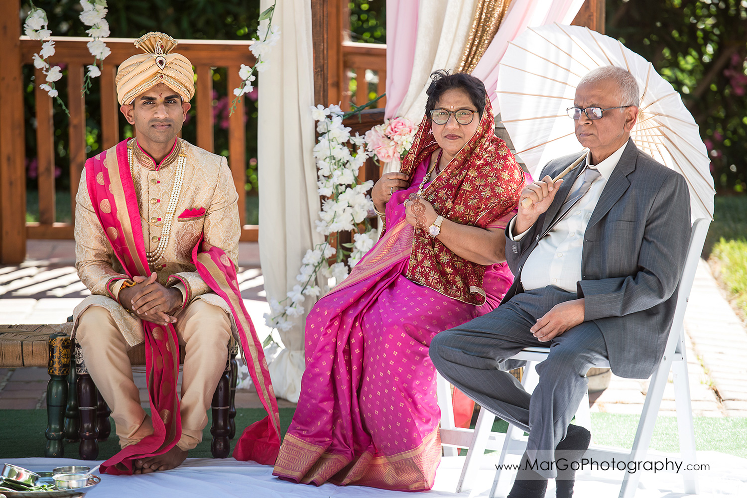Indian groom with his parents sitting under mandap during wedding ceremony at Elliston Vineyards in Sunol