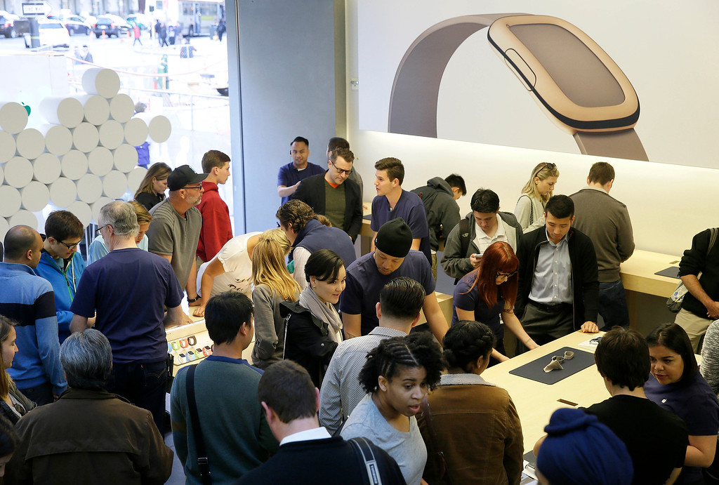 . Customers look at Apple\'s new watch at a store in San Francisco, Friday, April 10, 2015. Apple has started taking orders for the watch on its website and the Apple Store app. Currently, that\'s the only way Apple is selling the watch, with shipments scheduled to start April 24. (AP Photo/Eric Risberg)