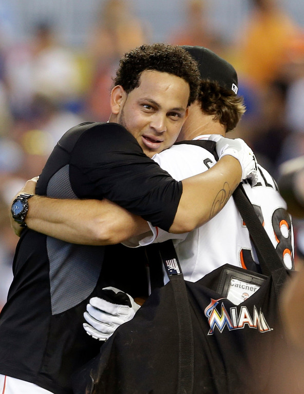 . Miami Marlins\' Henderson Alvarez, left, is hugged by bullpen coach Reid Cornelius (38) after pitching a no-hitter against the Detroit Tigers in an interleague baseball game on Sunday, Sept. 29, 2013, in Miami. The Marlins won 1-0. (AP Photo/Alan Diaz)