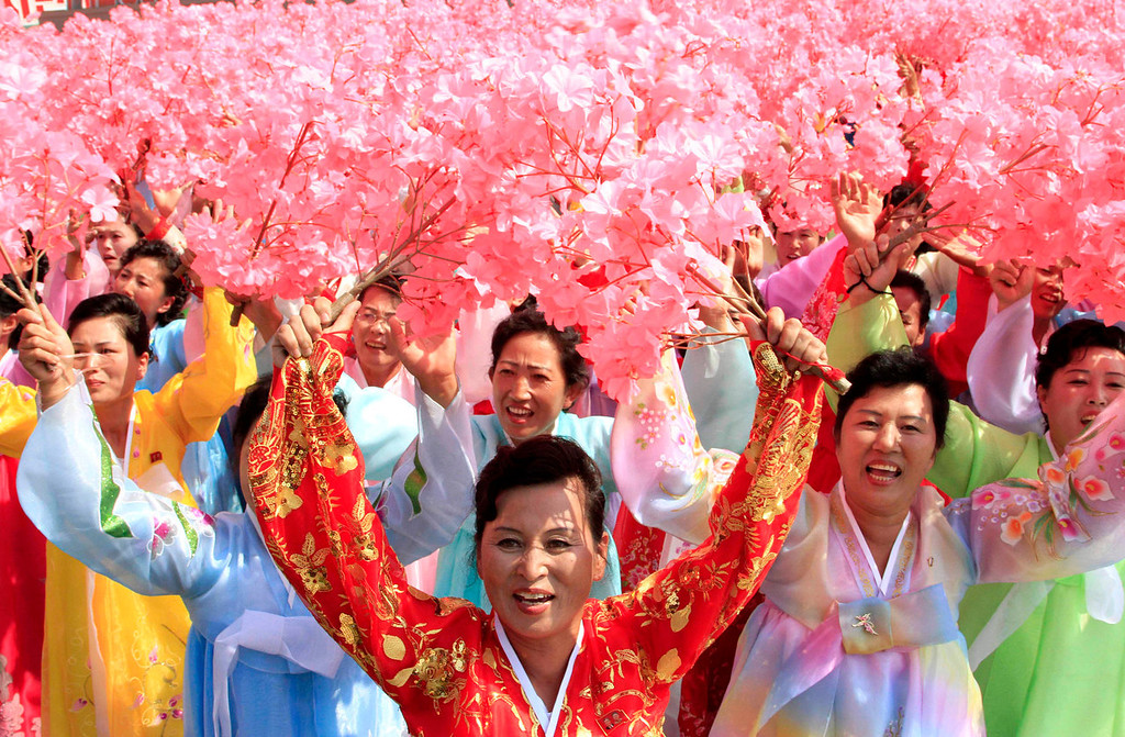 . North Korean women hold up flowers during a military parade at Kim Il Sung Square to mark the 65th anniversary of the country\'s founding in Pyongyang, North Korea, Monday, Sept. 9, 2013. (AP Photo/Jon Chol Jin)