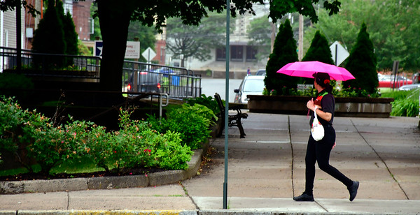6/25/2019 Mike Orazzi | Staff A pedestrian shields herself from rain in downtown Bristol along North Main Street Tuesday afternoon.