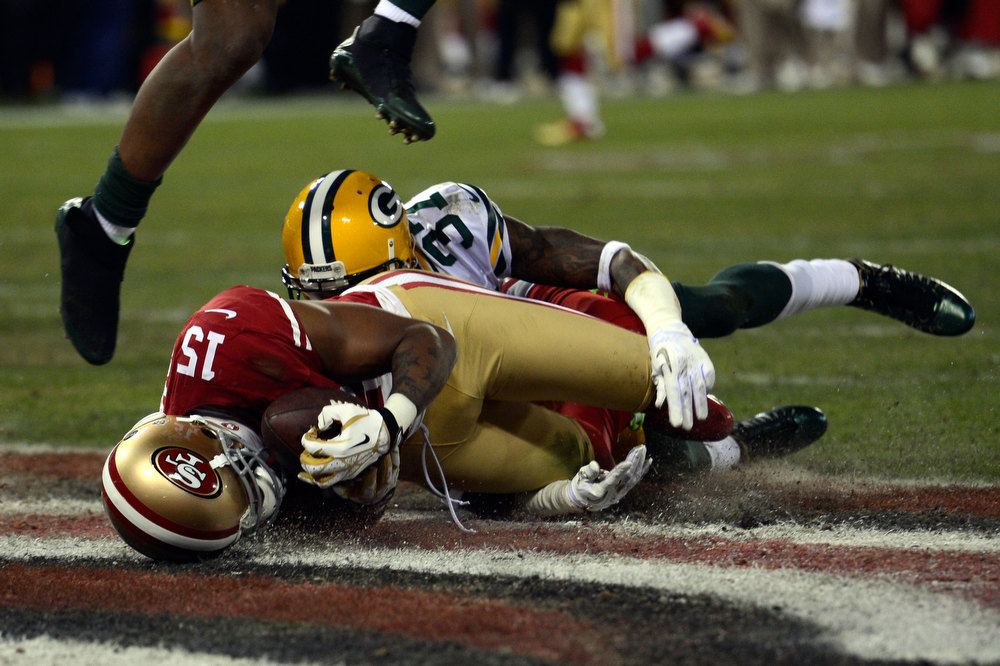 Description of . Wide receiver Michael Crabtree #15 of the San Francisco 49ers catches a touchdown pass thrown by quarterback Colin Kaepernick #7 against cornerback Sam Shields #37 of the Green Bay Packers in the second quarter during the NFC Divisional Playoff Game at Candlestick Park on January 12, 2013 in San Francisco, California.  (Photo by Thearon W. Henderson/Getty Images)