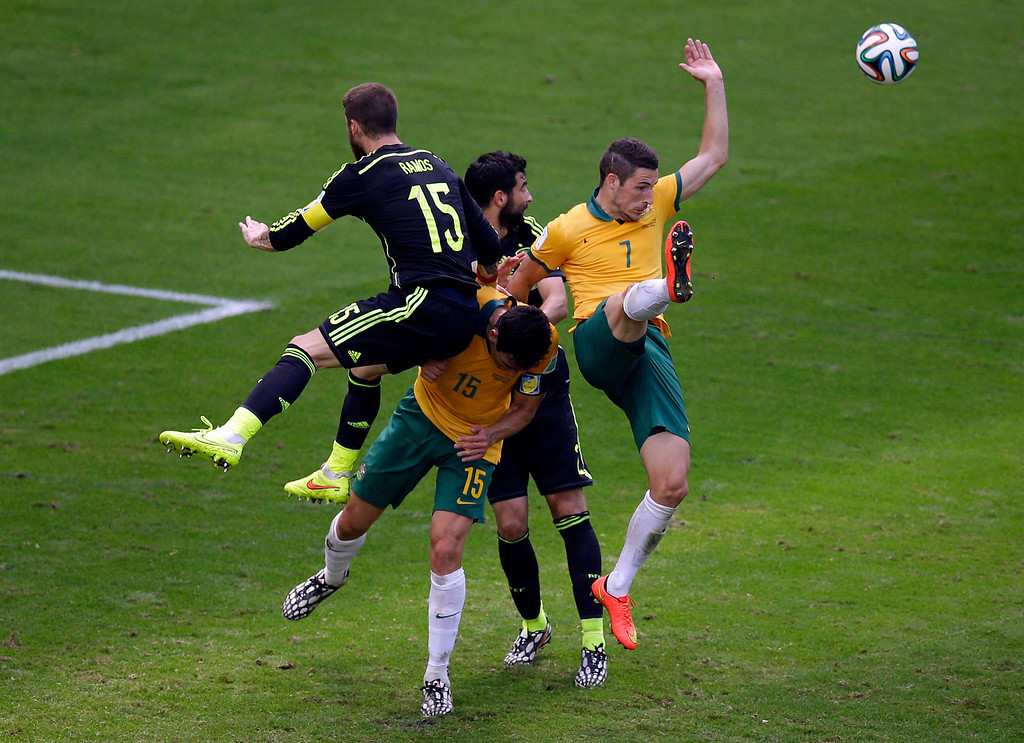 . Australia\'s Mathew Leckie, right, goes for the ball during the group B World Cup soccer match between Australia and Spain at the Arena da Baixada in Curitiba, Brazil, Monday, June 23, 2014. (AP Photo/Michael Sohn)