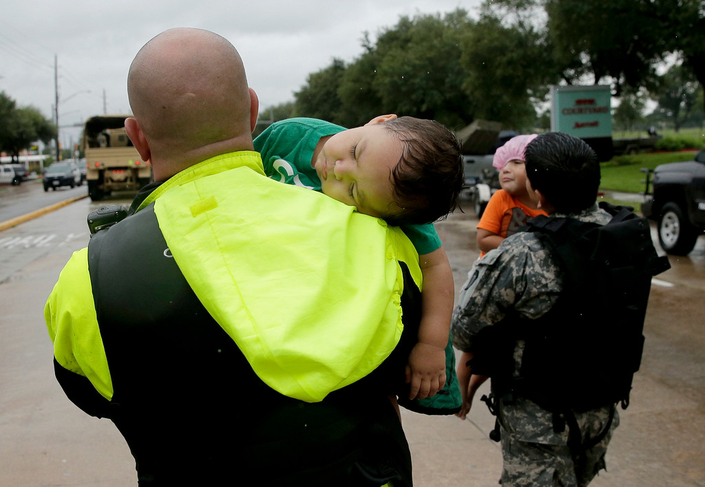 . Rescue personnel carry Avelia Lopez, left, and his brother Daniel to dry ground as people evacuate a neighborhood that was inundated after water was released from nearby Addicks Reservoir when it reached capacity due to Tropical Storm Harvey on Tuesday, Aug. 29, 2017, in Houston, Texas. (AP Photo/Charlie Riedel)