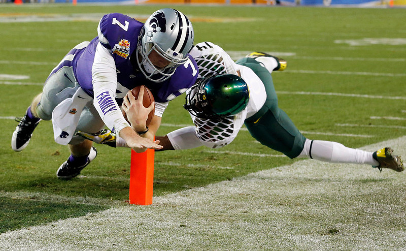 . Kansas State quarterback Collin Klein (7) dives for a touchdown as Oregon cornerback Ifo Ekpre-Olomu (14) defends during the first half of the Fiesta Bowl NCAA college football game, Thursday, Jan. 3, 2013, in Glendale, Ariz. (AP Photo/Ross D. Franklin)