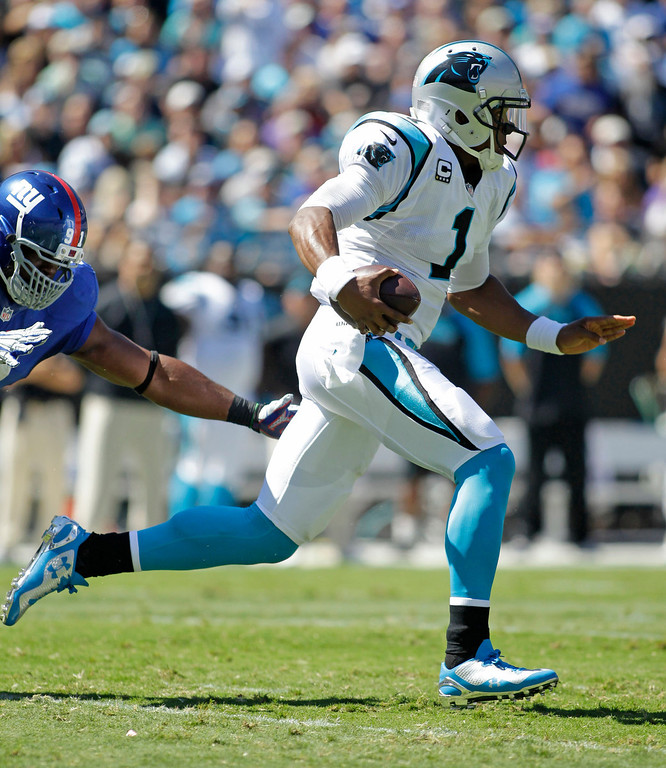 . Carolina Panthers quarterback Cam Newton (1) scrambles past New York Giants defensive end Justin Tuck (91) during the first half of an NFL football game in Charlotte, N.C., Sunday, Sept. 22, 2013. (AP Photo/Bob Leverone)