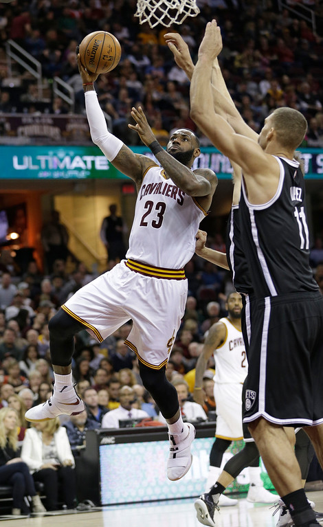 . Cleveland Cavaliers\' LeBron James (23) drives against Brooklyn Nets\' Brook Lopez (11) in the second half of an NBA basketball game, Friday, Dec. 23, 2016, in Cleveland. (AP Photo/Tony Dejak)
