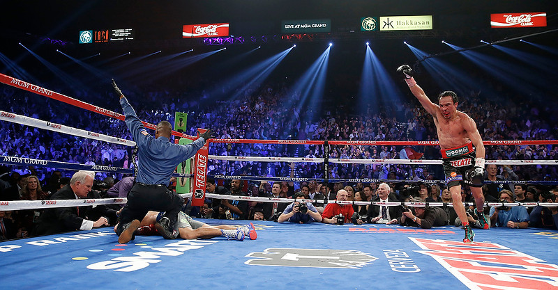 . Referee Kenny Bayless, left, calls the fight as Juan Manuel Marquez, from Mexico, right, celebrates after he knocked out Manny Pacquiao, from the Philippines, lower left, in the sixth round of their WBO world welterweight  fight Saturday, Dec. 8, 2012, in Las Vegas. (AP Photo/Eric Jamison)