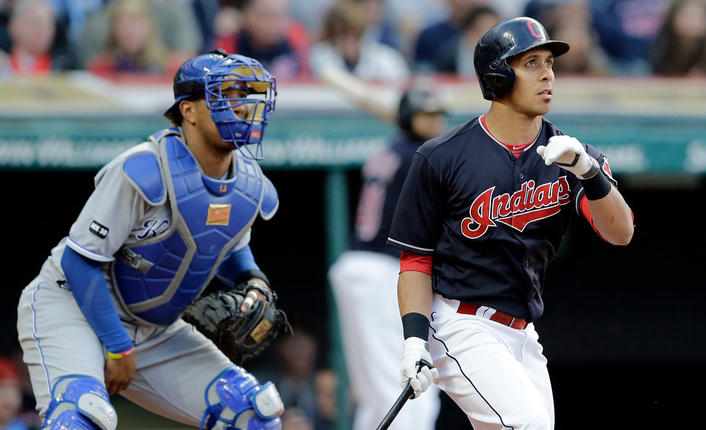 . Cleveland Indians\' Michael Brantley, left, watches his RBI-single off Kansas City Royals starting pitcher Ian Kennedy in the third inning of a baseball game, Friday, May 26, 2017, in Cleveland. Royals catcher Salvador Perez, left, watches. (AP Photo/Tony Dejak)