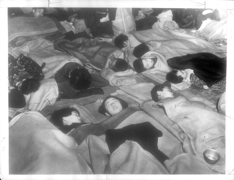 """""""The End of homecoming day finds arrivals from Communist China tucked in bed at reception center.  Leftists, planted among repatriates, demanded that they be allowed to leave at their will.""""--caption on photograph"""