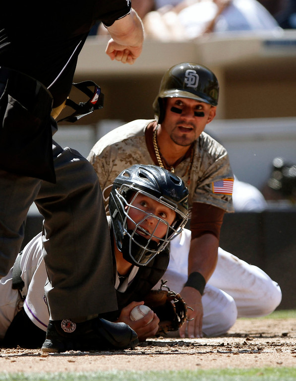 . Home plate umpire Todd Tichenor, left, calls San Diego Padres\' Reymond Fuentes, rear, out on the block tag by Colorado Rockies catcher Jordan Pacheco during the third inning of a baseball game on Sunday, Sept. 8, 2013, in San Diego. (AP Photo/Don Boomer)