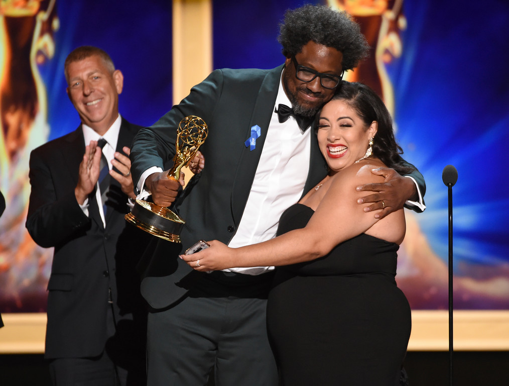 ". W. Kamau Bell, left, and Geraldine Porras accept the award for outstanding unstructured reality program for ""United Shades of America With W. Kamau Bell\"" during night two of the Television Academy\'s 2018 Creative Arts Emmy Awards at the Microsoft Theater on Sunday, Sept. 9, 2018, in Los Angeles. (Photo by Phil McCarten/Invision/AP)"