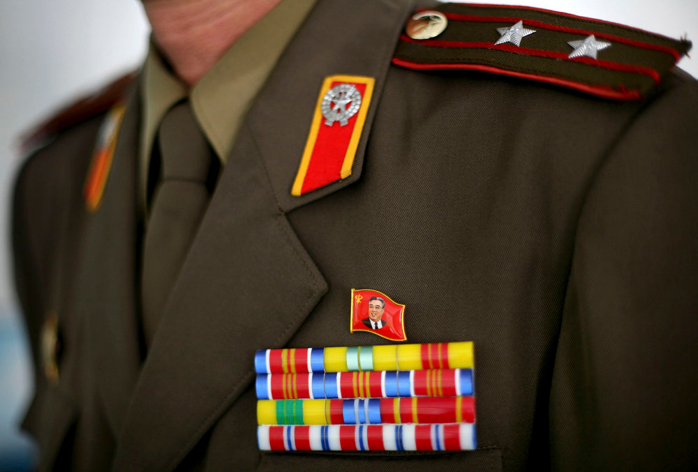 Description of . A pin showing a portrait of North Korea's founder Kim Il Sung is attached to the uniform of a North Korean Lieutenant along the Demilitarized Zone that separates the two halves of the Korean peninsula near Kaesong, North Korea on Thursday, Sept. 18, 2008.  (AP Photo/David Guttenfelder)
