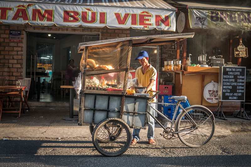 A street food vendor sets up his cart in the late afternoon.