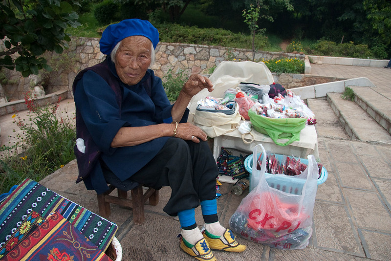 82-yr-old lady with bind feet selling gifts outside caves.  This custom was started during the Qiang Dynasty.  The Empress Dowager put this custom to a stop when she became ruler.