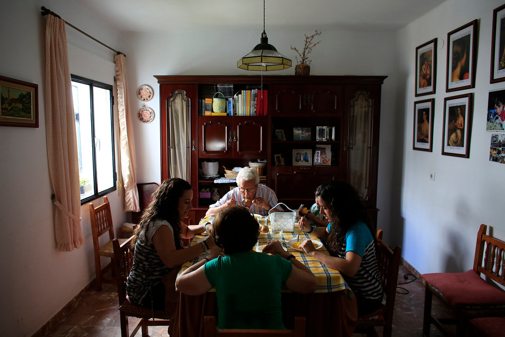 . Spanish nurses Maria Jose Marin (R), 23, her twin sister Maria Teresa (L), have lunch with their father Jose Manuel (top), 79, and mother Nati, 65, at their home in Paradas, southern Spain, June 3, 2013. After months of studying Dutch, a group of young Spanish nurses moved to the Netherlands to take up work, fleeing a dismal job market at home. Spain\'s population dropped last year for the first time on record as young professionals and immigrants who moved here during a construction boom head for greener pastures. Spain\'s jobless rate is 27 percent, and more than half of young workers are unemployed. For Spanish nurses, the Netherlands\' nursing deficit is a boon.Picture taken June 3, 2013.  REUTERS/Marcelo del Pozo