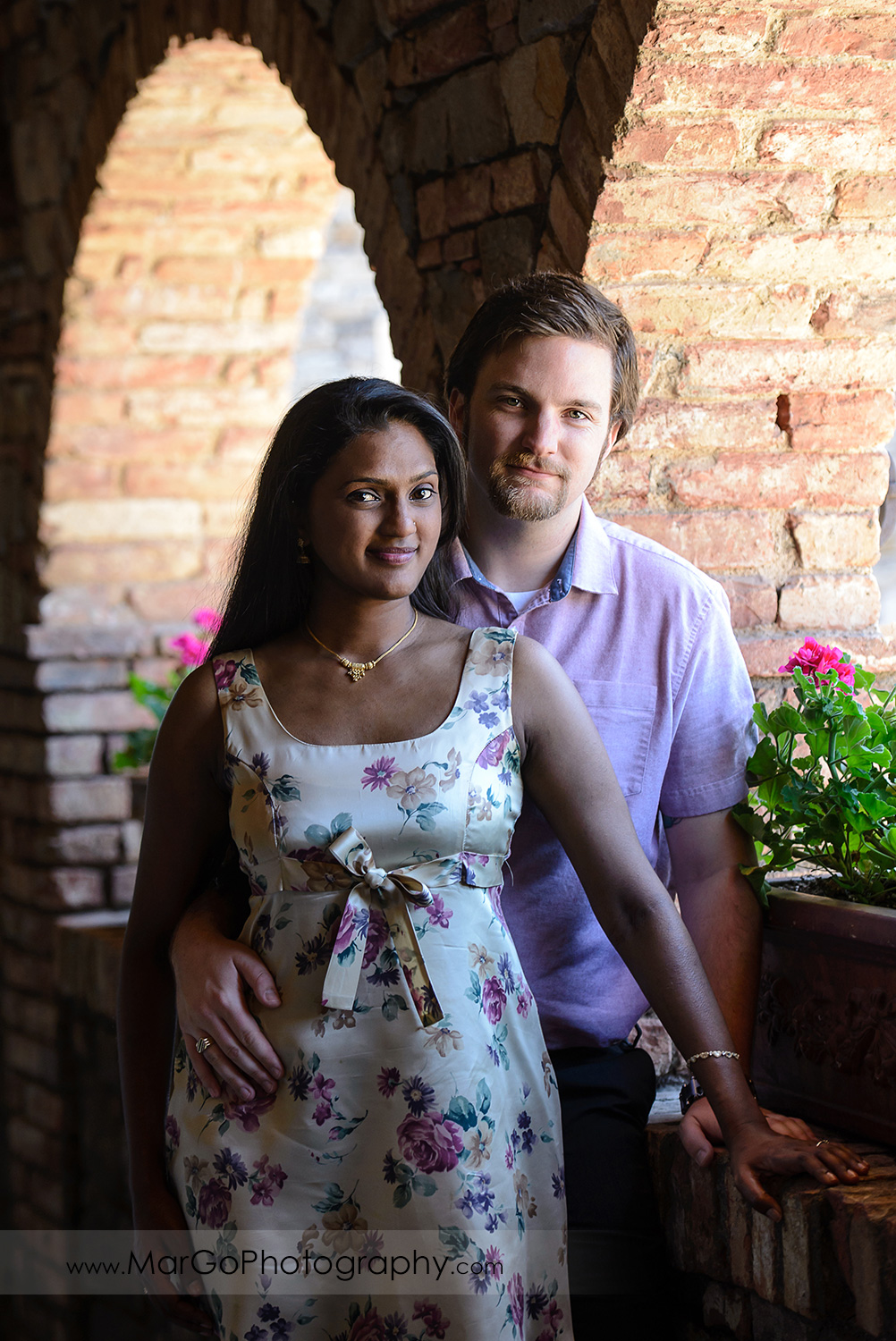 portrait of Indian woman in flower dress standing in front of man in pink shirt during engagement session at Castello di Amorosa in Calistoga