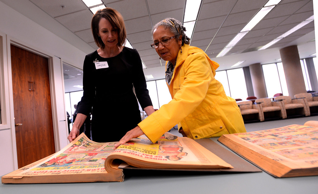 . Pam Langford, left, and Kathryn Ervin, right, view a bound copy of a 1939 edition of The San Bernardino Daily Sun at California State University San Bernardino April 8, 2013.  GABRIEL LUIS ACOSTA/STAFF PHOTOGRAPHER.