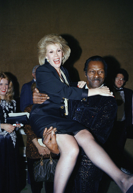 . Comedian Joan Rivers gets a lift from rock \'n\' roll legend Chuck Berry at the Library of the Performing Arts at Lincoln Center in New York, Feb. 17, 1988. Rivers and Berry were joined by other stars for the presentation of the D.W. Griffith Awards by the National Board of Review of Motion Pictures. (AP Photo/Wilbur Funches)