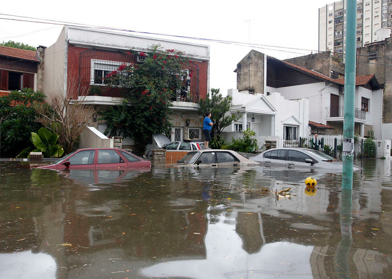 . A man looks at cars in a flooded street after a rainstorm in Buenos Aires April 2, 2013. Thunderstorms damaged property and vehicles, cut power and caused delays on flights in Buenos Aires and its suburbs. The City\'s SAME emergency service announced that the death toll has risen to five.   REUTERS/Enrique Marcarian