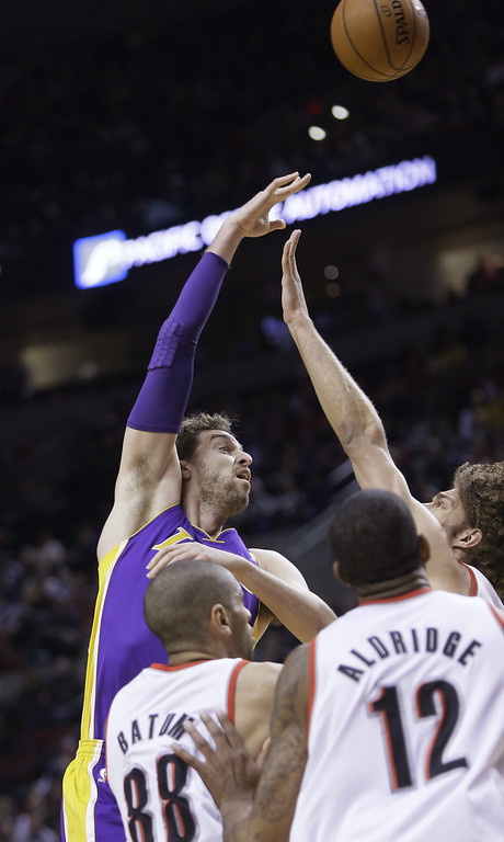 . Los Angeles Lakers center Pau Gasol, from Spain, left, shoots over the Portland Trail Blazers,  from right, Robin Lopez, LaMarcus Aldridge and Nicolas Batum, from France, during the first half of an NBA basketball game in Portland, Ore., Monday, March 3, 2014.(AP Photo/Don Ryan)