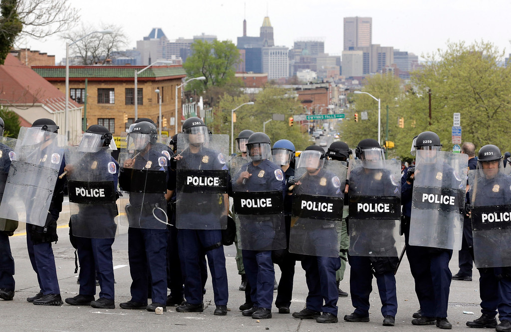 . Police stand in formation in response to demonstrators who were throwing objects at police, Monday, April 27, 2015, after the funeral of Freddie Gray in Baltimore. Gray died from spinal injuries about a week after he was arrested and transported in a Baltimore Police Department van. (AP Photo/Patrick Semansky)