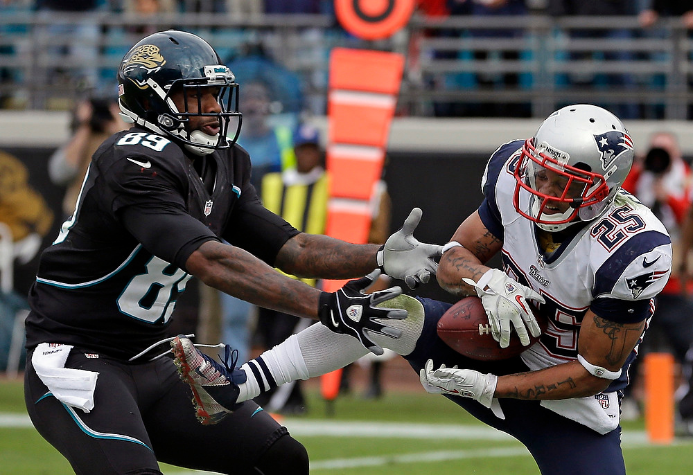 . New England Patriots free safety Patrick Chung, right, intercepts a pass in front of Jacksonville Jaguars tight end Marcedes Lewis (89) as time expires in an NFL football game on Sunday, Dec.  23, 2012, in Jacksonville, Fla. New England won the game 23-16. (AP Photo/John Raoux)