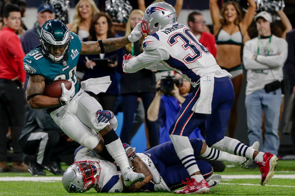 . Philadelphia Eagles running back Corey Clement (30), is tackled by New England Patriots outside linebacker Elandon Roberts (52), bottom, and strong safety Duron Harmon (30), during the first half of the NFL Super Bowl 52 football game, Sunday, Feb. 4, 2018, in Minneapolis. (AP Photo/Frank Franklin II)