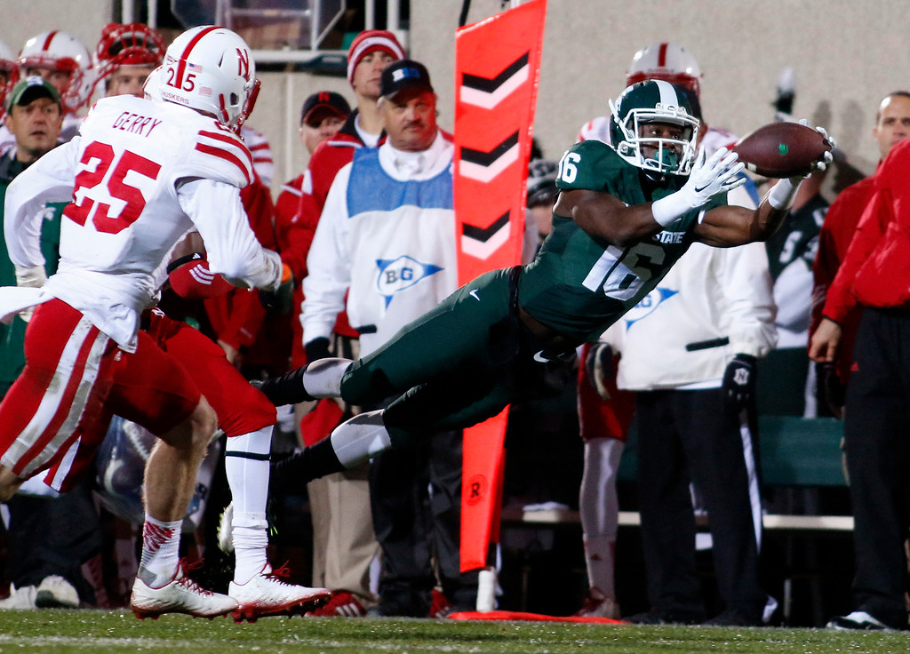 . Michigan State receiver Aaron Burbridge (16) dives for a pass against Nebraska\'s Nate Gerry (25) during the second quarter of an NCAA college football game, Saturday, Oct. 4, 2014, in East Lansing, Mich. The pass fell incomplete. (AP Photo/Al Goldis)