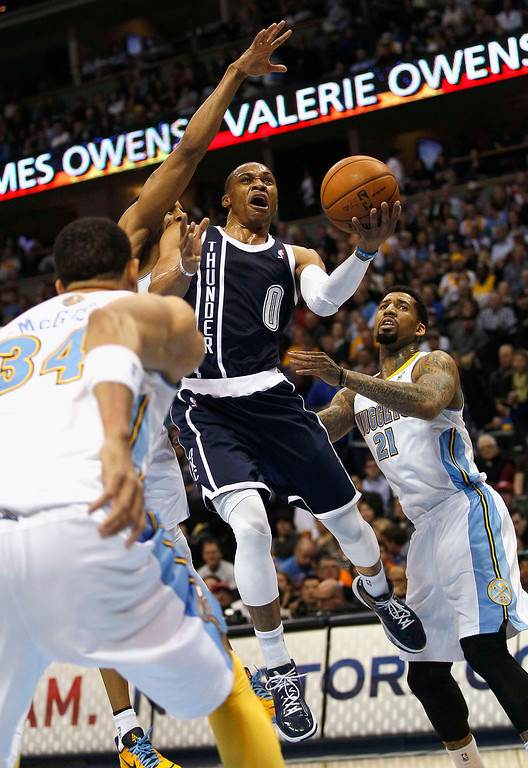 . Oklahoma City Thunder guard Russell Westbrook drives to the hoop past Denver Nuggets\' JaVale McGee (L) and Wilson Chandler in their NBA basketball game in Denver March 1, 2013. REUTERS/Rick Wilking