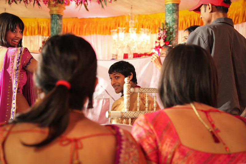 The groom behind a sheet as he waits to see his bride.