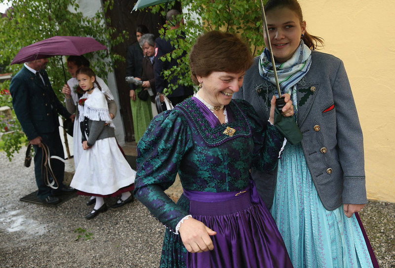 . Participants wearing traditional Bavarian folk costumes pull out umbrellas against drizzling rain after attending the annual Corpus Christi (in German called Fronleichnam) mass at St. Michael\'s Church on May 30, 2013 in Seehausen am Staffelsee, Germany. The Seehausen Corpus Christi celebration usually includes a procession to a chapel across the nearby Staffelsee lake, though rain forced organizers to cancel the lake procession this year. Corpus Christi is among the highlights of the Catholic religious calendar in Bavaria.  (Photo by Sean Gallup/Getty Images)