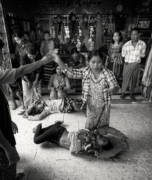 Burmese believe in Spirits called Nats. This spirits although mostly humans from the past who experienced a violent death can also be natural objects or animals. Nats can possess people with different results depending on the Nat. In the image the young girls are believed to have been posed by an angry dragon Nat; hens their uncontrollable behavior.  Mandalay, Myanmar 2017