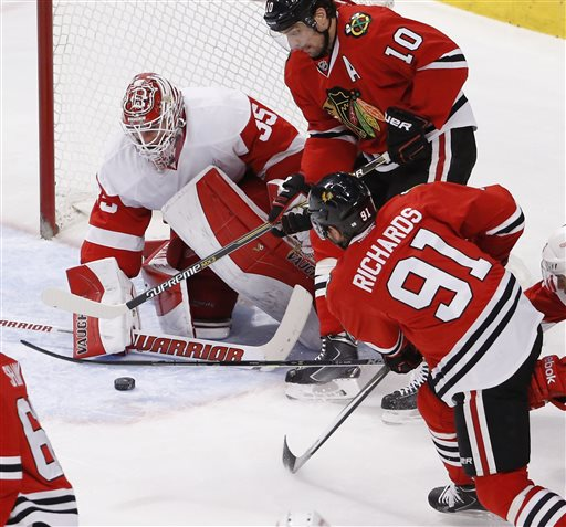 . Detroit Red Wings goalie Jimmy Howard (35) makes a save on a shot by Brad Richards (91) as Patrick Sharp (10) watches during the second period of an NHL hockey game Wednesday, Feb. 18, 2015, in Chicago. (AP Photo/Charles Rex Arbogast)