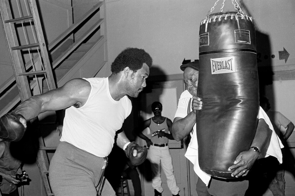 . Heavyweight champion George Foreman winds up a right as he works out on the heavy bag on August 7, 1974 at his training camp at the Alameda County Fairgrounds in Pleasanton, California. That?s trainer Dick Sadler hanging onto the bag. Foreman is in training for a defense of his title against Muhammad Ali in September. The fight will be in Africa. (AP Photo/Robert Houston)
