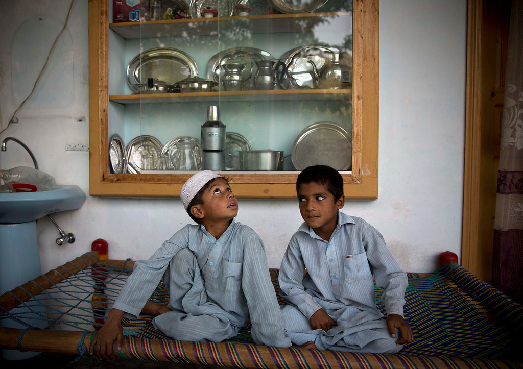 """. Haroon, 5, left, and Abdul Hamid, 8, neighbors of the man who is accused of shooting Malala Yousufzai a year ago, sit in his home in Ghawari Mastas, Swat Valley, Pakistan on Thursday, Oct. 3, 2013. Military officials say Malala\'s assailant Attaullah, has fled to Afghanistan, while the police say the case is closed. In a rare interview, Attaullah\'s sister told The Associated Press: \""""We don\'t know where he is, whether he is dead or alive.\"""" (AP Photo/Anja Niedringhaus)"""