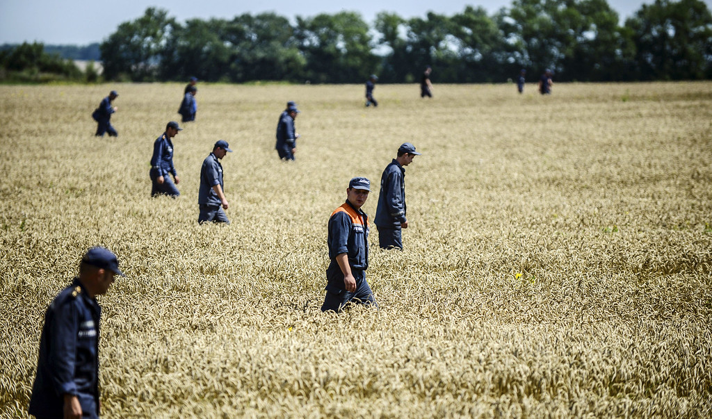 . Members of the  Ukrainian State Emergency Service search for bodies in a field near the crash site of the Malaysia Airlines Flight MH17 near the village of Hrabove (Grabove), in Donetsk region on July 26, 2014. AFP PHOTO/ BULENT  KILIC/AFP/Getty Images
