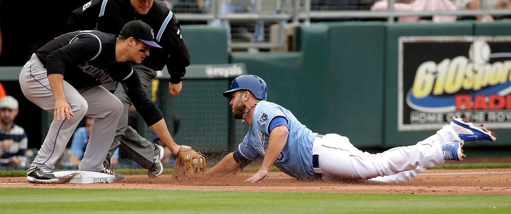 . Kansas City Royals\' Mike Moustakas is out at third by Colorado Rockies third baseman Nolan Arenado as he tried to steal during the second inning of a baseball game Wednesday, May 14, 2014 in Kansas City, Mo. (AP Photo/Charlie Riedel)