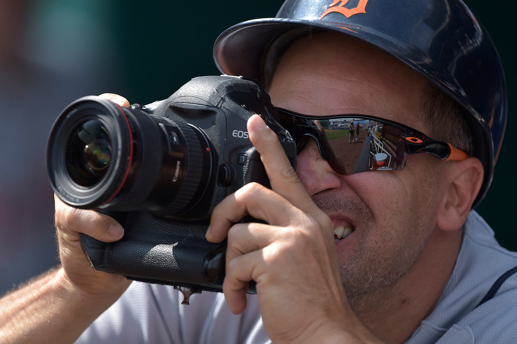 . Detroit Tigers first base coach Omar Vizquel (31) tries out a photographer\'s camera before the start of their  baseball game against the Kansas City Royals, Saturday, Sept. 20, 2014, in Kansas City, Mo. (AP Photo/Reed Hoffmann)