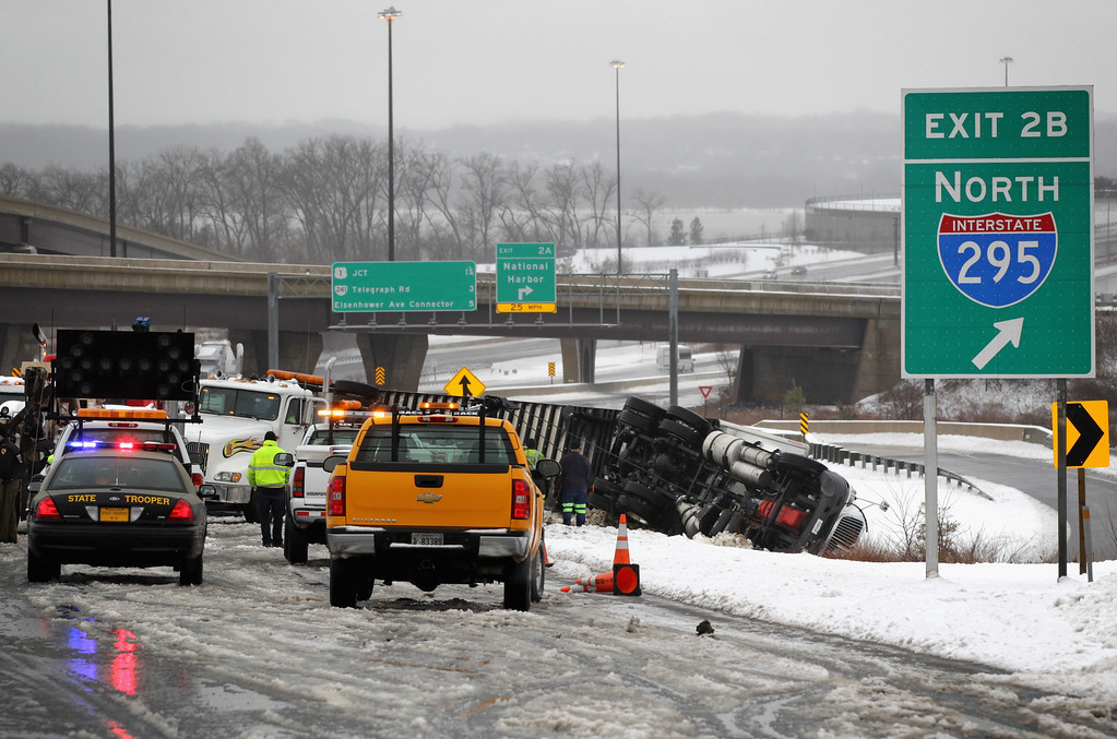 . Rescue workers are at the scene of an overturned tractor trailer on inner loop of the I-495 February 13, 2014 in Oxon Hill, Maryland. Up to 12 inches of snow fell over the Washington area causing WMATA to cancel bus service but rail service continued to operate. (Photo by Alex Wong/Getty Images)