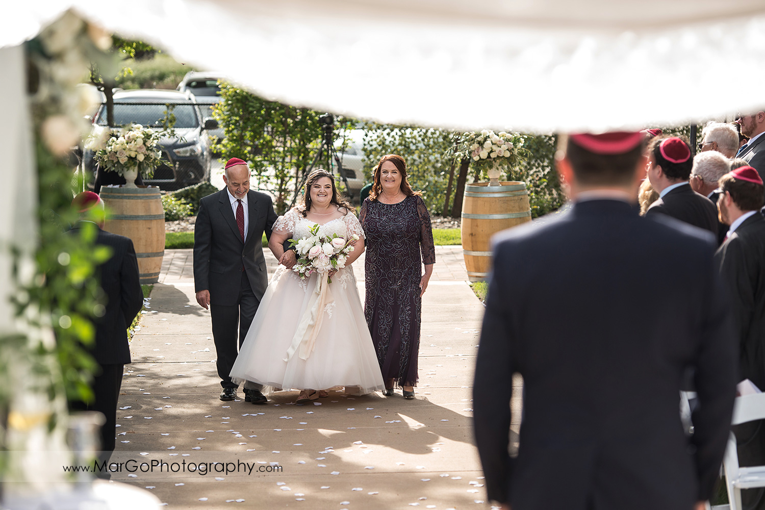 jewish bride walking down the aisle with her parrents during wedding ceremony at Livermore Garre Vineyard and Winery